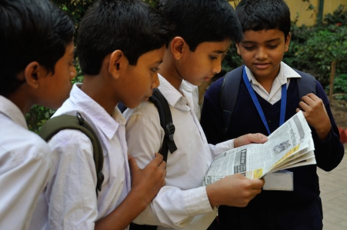 Students reading a newspaper together in Murshidabad